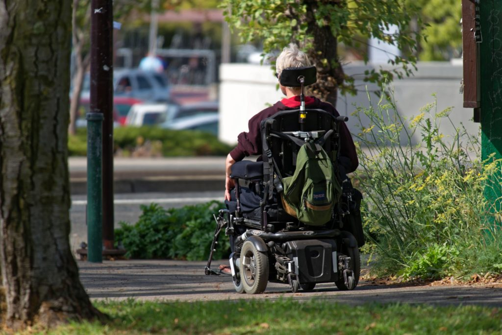 man outside cruising in lightweight electric wheelchair